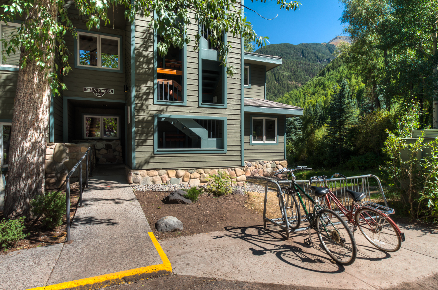 Front Exterior of green sided building with bike rack