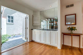Accordion door near bar in living room creating a seamless indoor/outdoor experience.