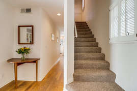 Stairs near front door leading upstairs to the bedrooms.