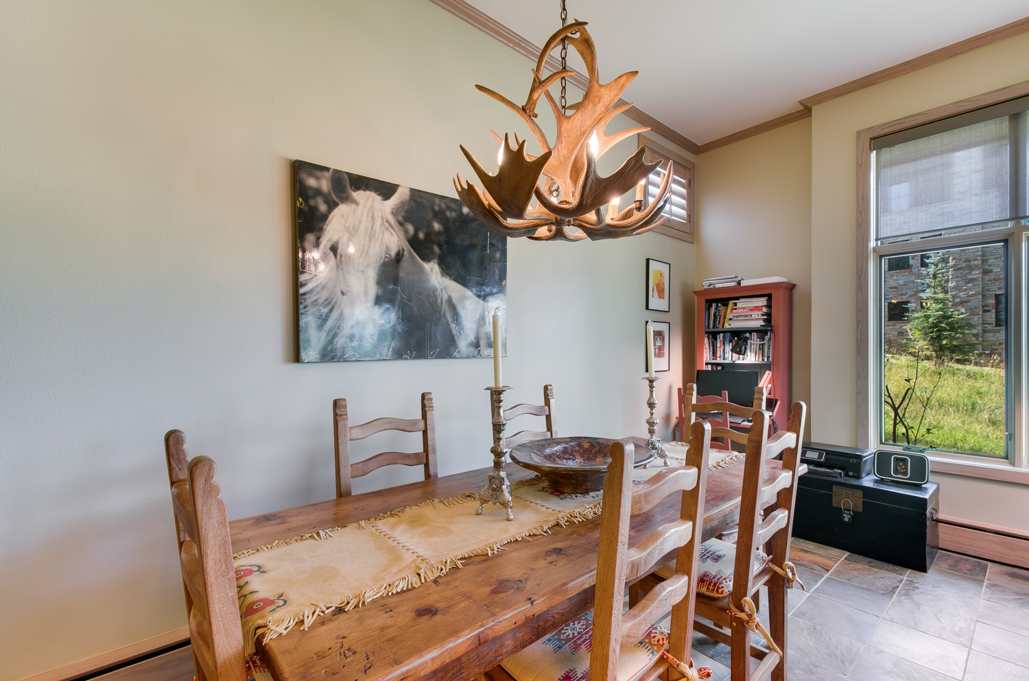 Wood dining table with antler chandelier