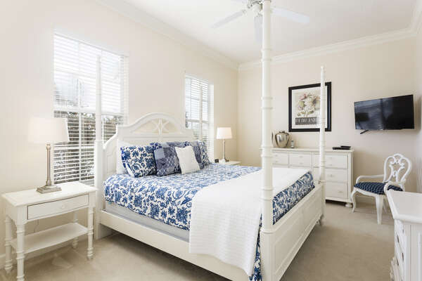 The master bedroom has a beautiful four post king bed with a wall mounted flat screen TV