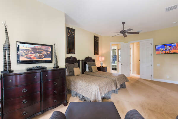 Upstairs bedroom with two twin beds, 32-inch TV, and another 40-inch TV