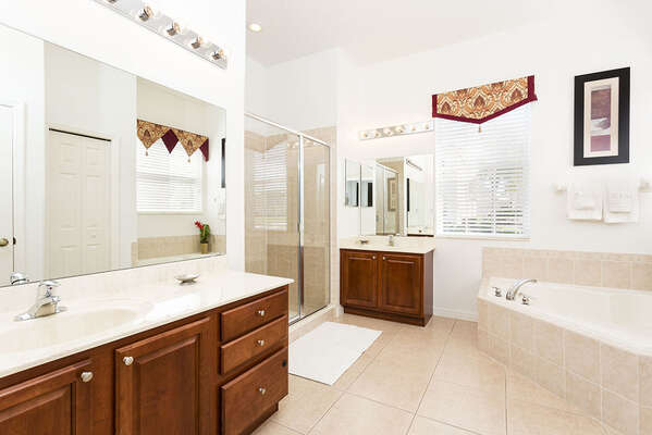 Master en-suite bathroom with dual sinks, bath tub and a separate shower