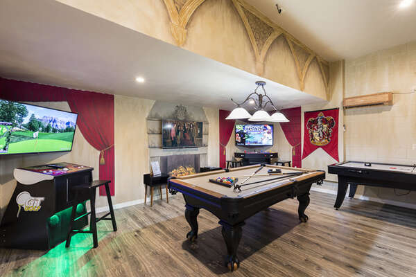 The game room with a pool table, an air hockey table, a golden tee golf, and multi-arcade with 10,000 games