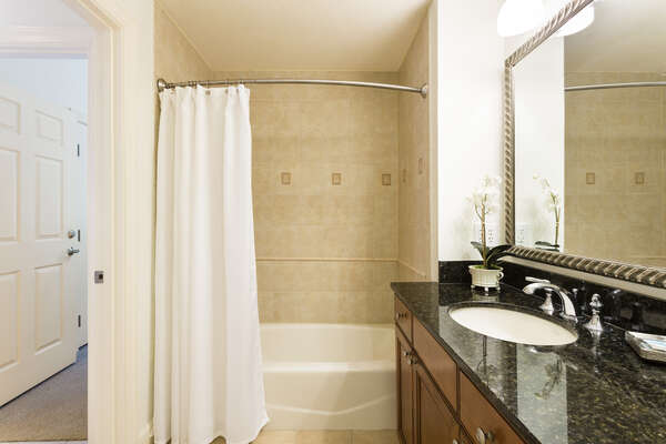 Granite counter tops, large mirror and a tub/shower combination can be found in the third bathroom
