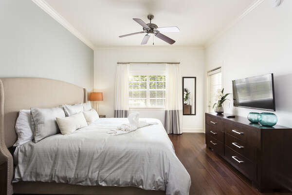 The master bedroom has a king bed along with a flat-screen TV and hardwood floors