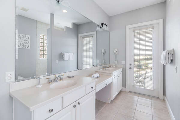 The ensuite master bathroom has beautiful natural light and access to the private balcony