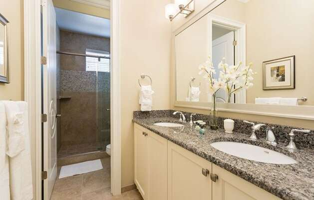 Granite countertops with dual sinks with walk-in glass shower.