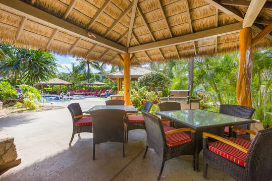 Cabana with Outdoor Dining Sets and Grill by the Pool.