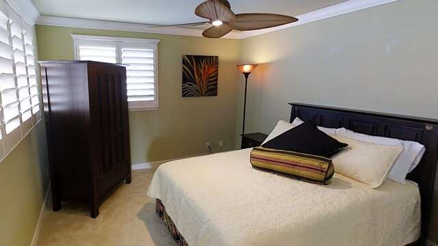 Bedroom with Large Bed, Wardrobe, Lamp, Nightstands, and Ceiling Fan.