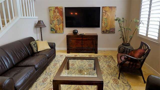 Living Area with Sofa, Chair, Coffee Table, TV Stand, and TV.