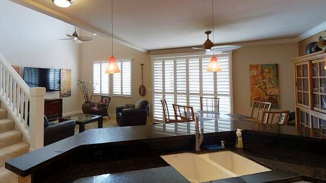 Kitchen Bar with Sink, Dining, and Living Area with Ceiling Fans.