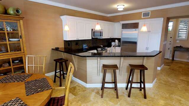 Kitchen with Bar, Stools, Refrigerator, Microwave, Dining Table, and Chairs.