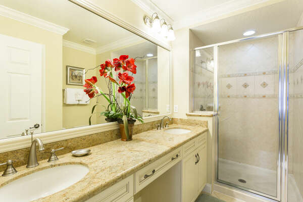 The master bathroom offers dual sinks, granite countertops, and a walk-in shower