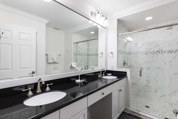 The ensuite master bathroom features a walk-in shower and his and her sinks