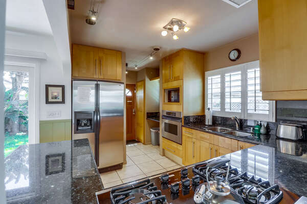Fully stocked kitchen with countertop stove and refrigerator