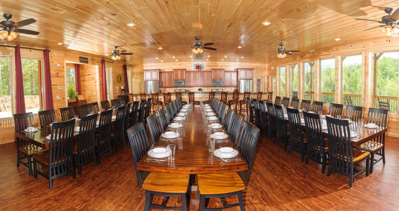 Big Dining Room with Tables, Chairs, Stools, Ceiling Fans,  Microwaves, and Refrigerators.