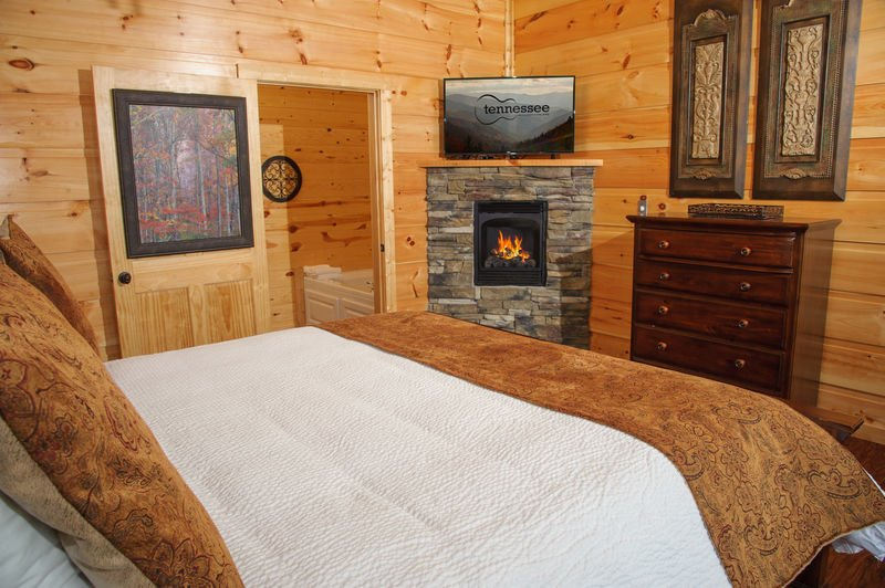 Bedroom with Large Bed, Fireplace, Dresser, and TV.
