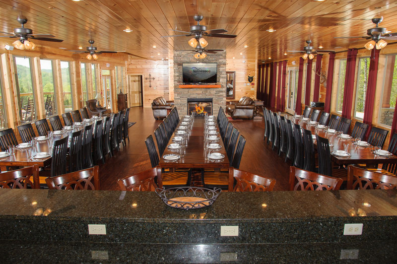 Big Dining Room with Tables, Chairs, Fireplace, and TV.