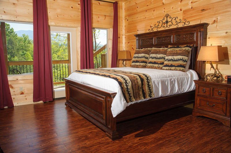 Large Bed, Nightstands, Table Lamps, Curtains, and Windows.