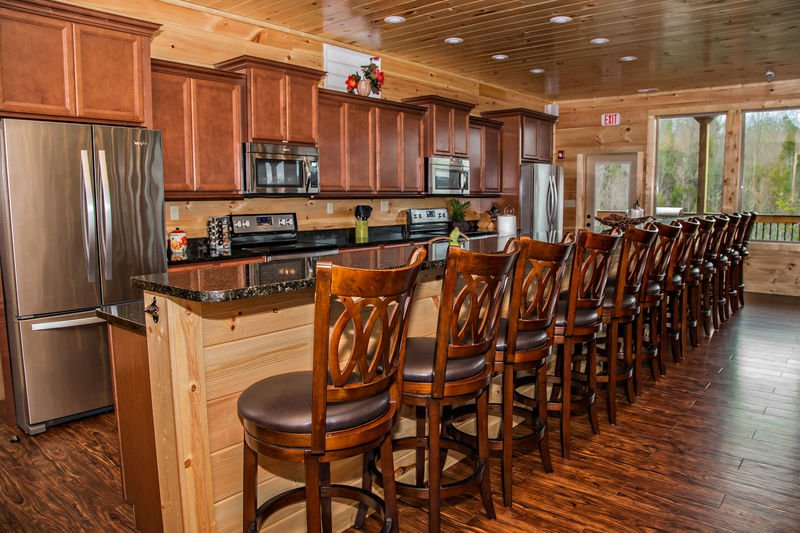 Kitchen with Breakfast Bar, Stools, Two Refrigerators, Two Microwaves, and Two Stoves.