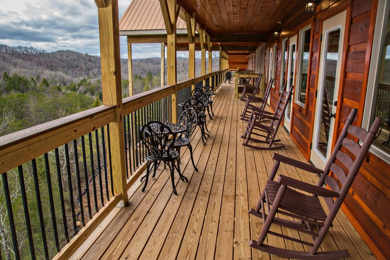 Large Deck with Many Outdoor Tables, Chairs, and Rocking Chairs.