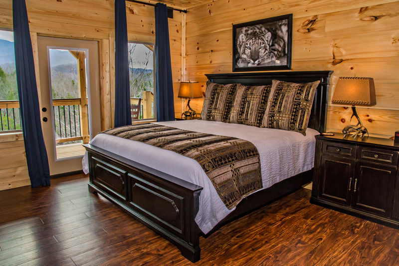 Bedroom with Large Bed, Dresser, Nightstands, Lamps, and Window Door to the Balcony.