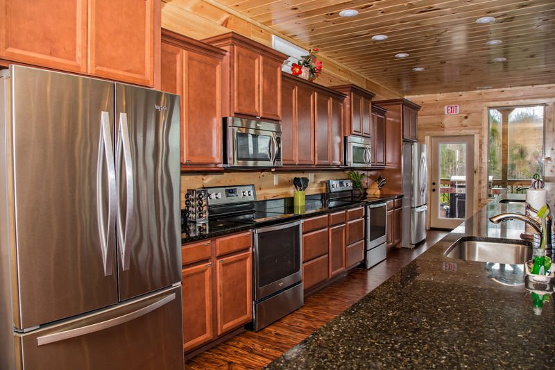 Kitchen with Two Refrigerators, Two Microwaves, and Two Stoves.