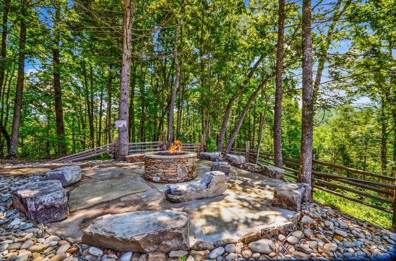 Gathering Area with Fire Pit, Rock Garden Benches, and Trees.