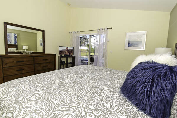 Master bedroom has a king bed, patio doors to the pool area and flatscreen TV