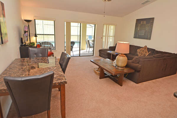 Family seating area with leather sofas, occasional table, patio doors flatscreen TV & DVD