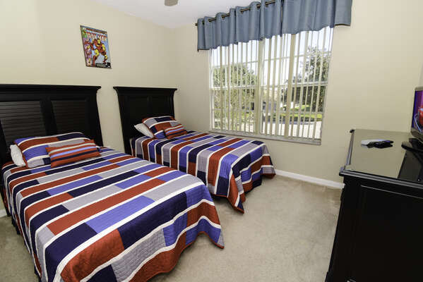 Bedroom 2 has twin beds and a flatscreen TV