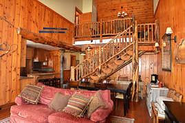 The custom log stairway and railing lead upstairs to the loft.
