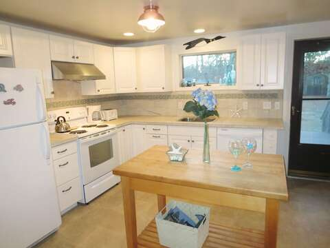 The kitchen has a door that leads you out to the deck and backyard - 156 Beach Plum Lane Brewster Cape Cod New England Vacation Rentals