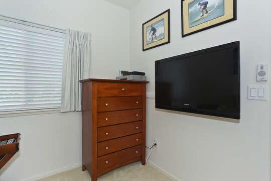 An Image of a Room with Tall Dresser and TV Mounted on Wall.