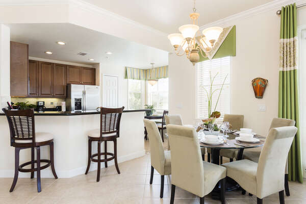 The dining area offers seating for 6 with 2 stools at the breakfast bar