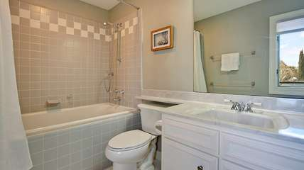 The bathroom has a jacuzzi tub and large vanity.