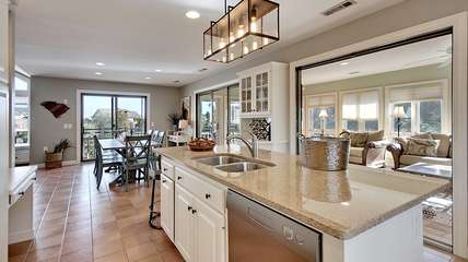 Granite counters, an island sink, and access to the sunroom are highlights.