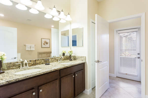 The master bathroom has easy access to the pool and plenty of space for him and her