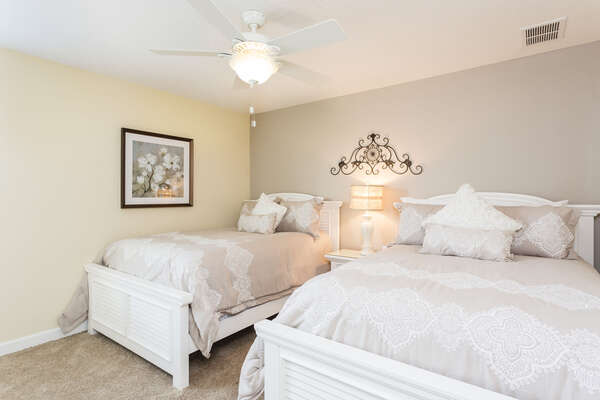 This upstairs bedroom is elegantly decorated with two full beds