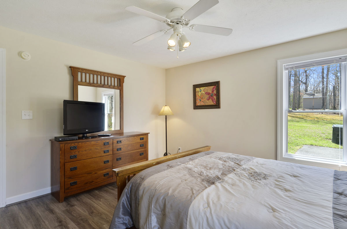 Main Level Bedroom with Queen Bed, TV, and Ceiling Fan