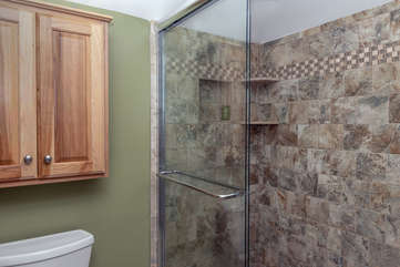 The shower is tiled and has a glass door.