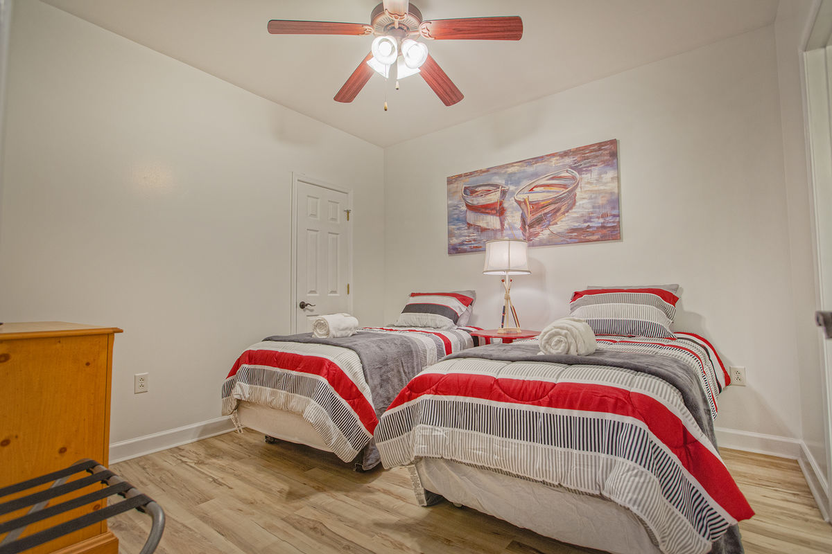 Bedroom with Two Beds, Ceiling Fan, and Dresser.