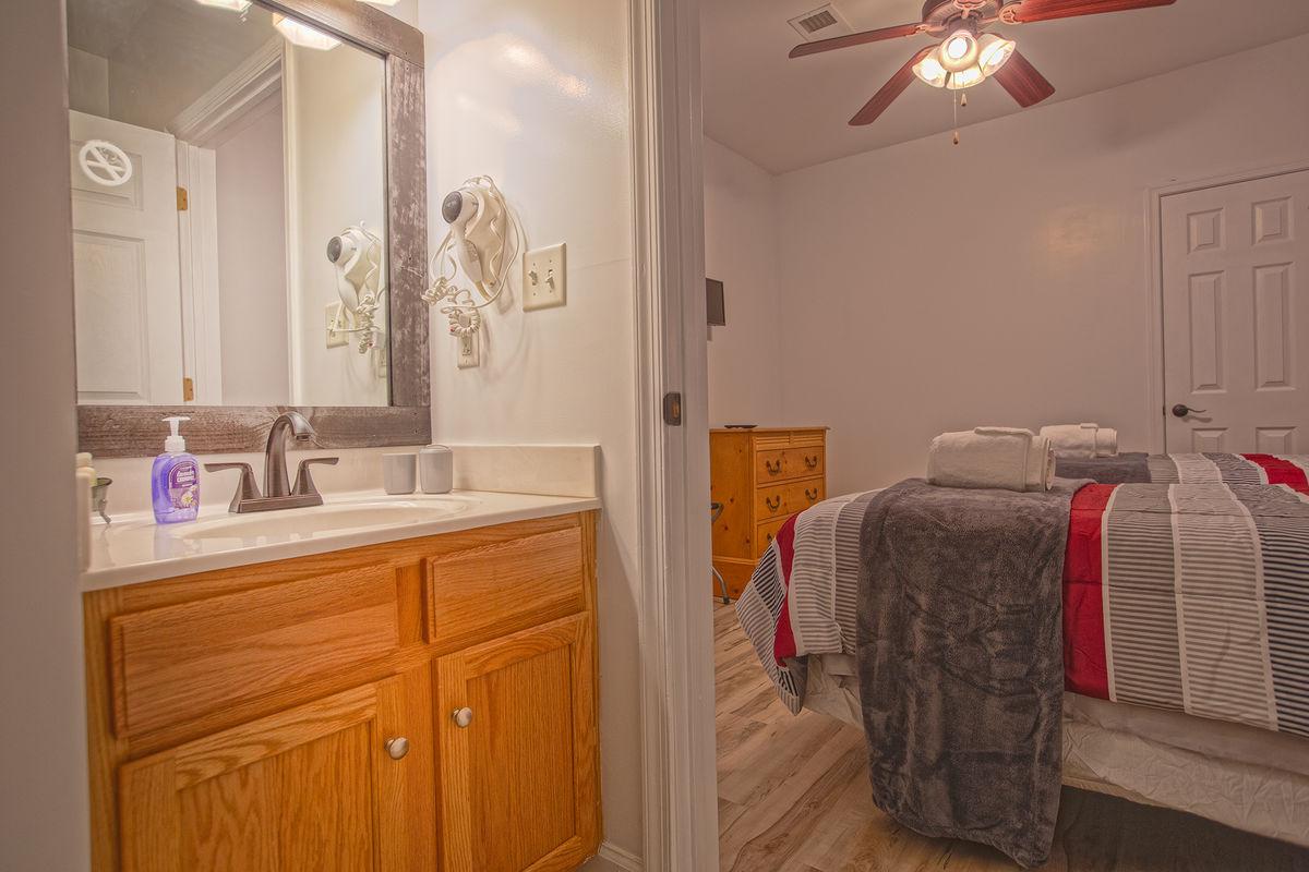 Single Vanity Sink, Mirror, Twin Beds, Ceiling Fan, and Dresser.Bat