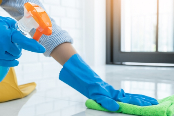 Person with blue gloves Disinfecting a counter