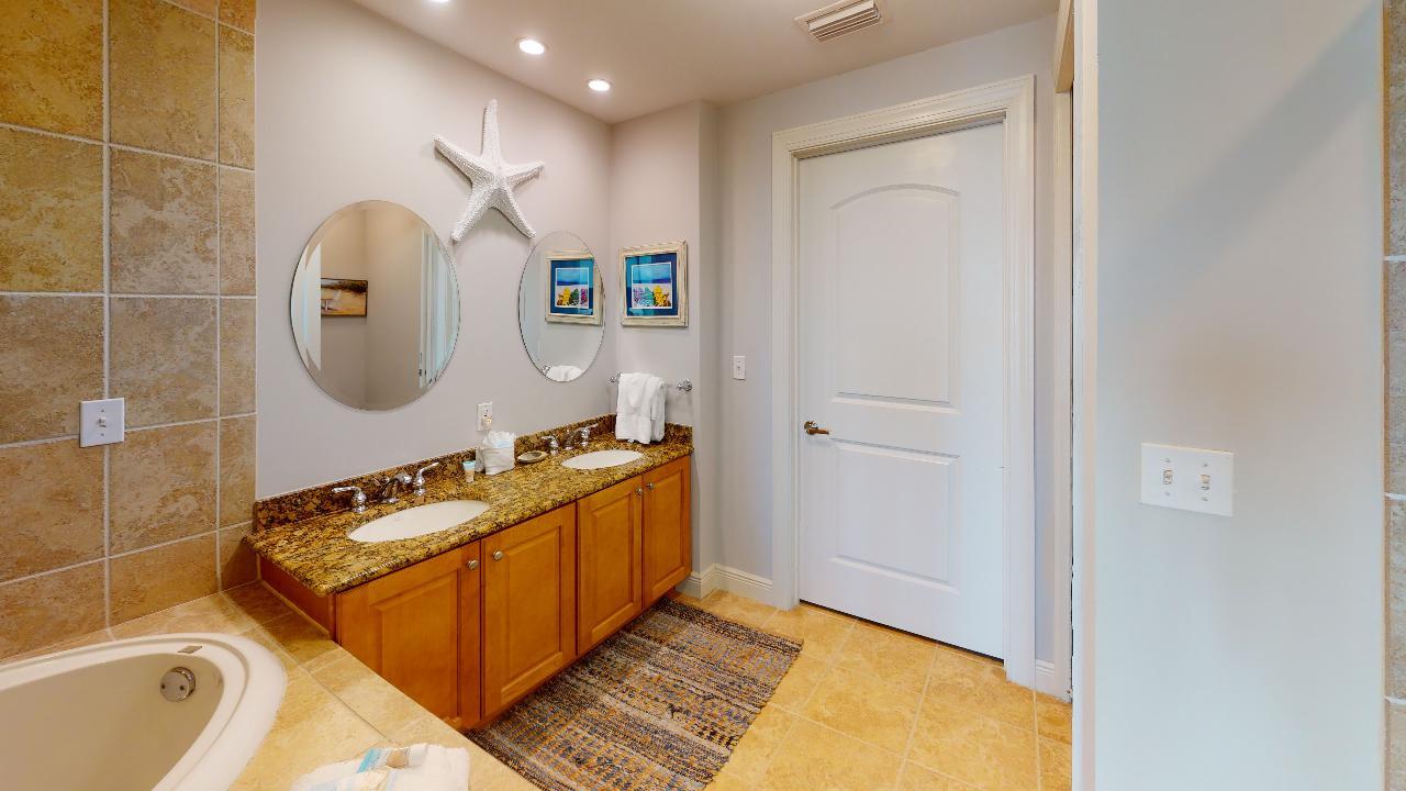 Double Sink Bathroom Vanity, Mirrors, and Jacuzzi Tub.