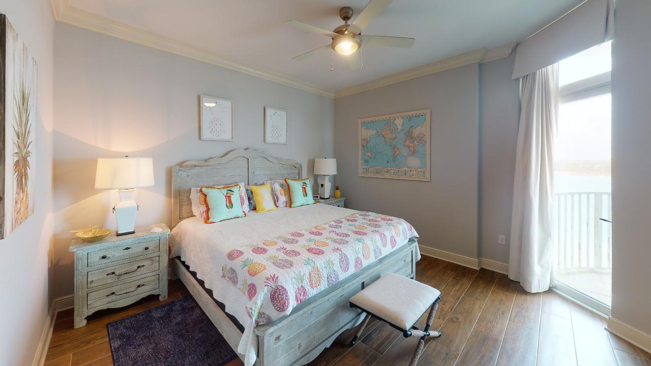 Large Bed, Nightstands, Table Lamps, Ceiling Fan, and Window Door.