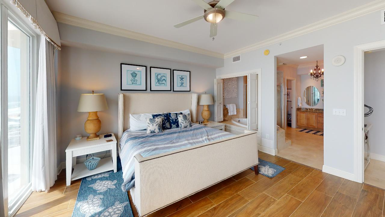Bedroom with Large Bed, Nightstands, Lamps, Windows, and Ceiling Fan.
