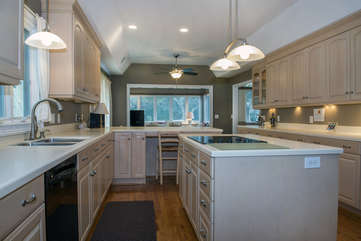 The island has a cooktop. Cabinets have under mount lighting.