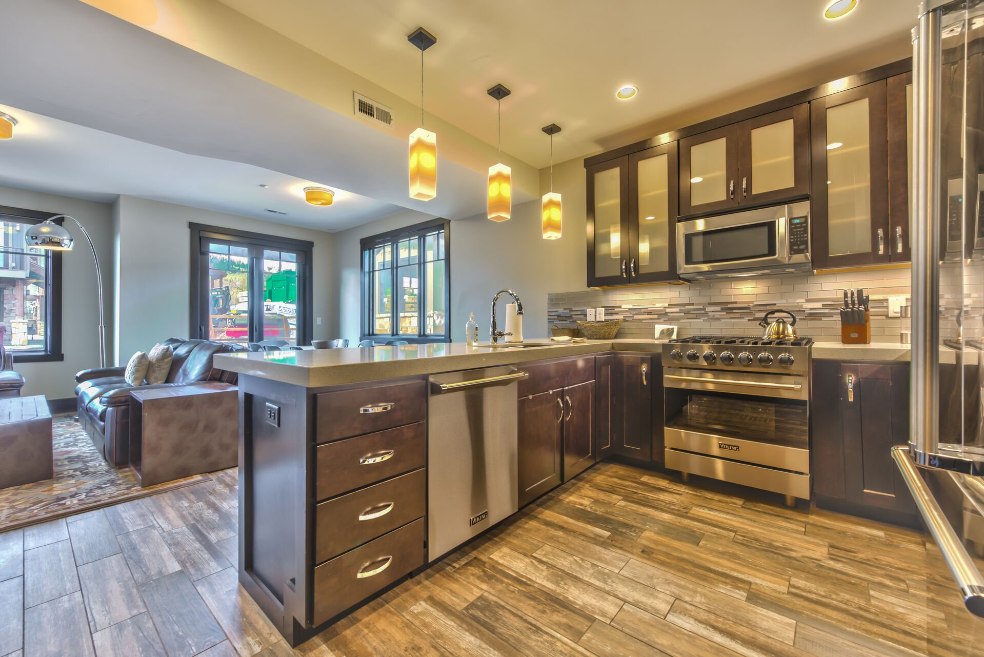 Fully Equipped Kitchen with Stainless Steel Appliances, a 6-Burner Viking Gas Range, Granite Countertops, Bar Seating for 4, Dining Area, and a Comfortable Living Room